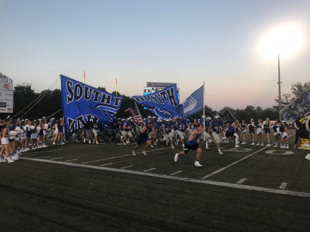 South Forsyth players burst onto the field filled with cheerleaders, Blue Crew Posse (BCP) members, and the South Forsyth mascot ahead of their game against Lassiter.