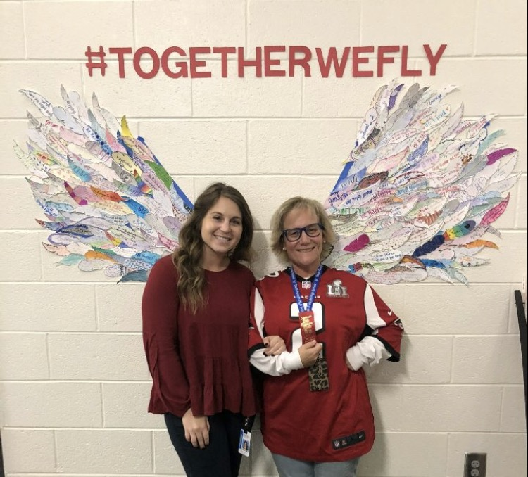 Mrs. Burnell and Ms. Frankel stand in front of wings constructed in the counselor's office from the feathers students made for Red Ribbon Week . The two counselors worked together on the events that occurred October 23 through the 30th.