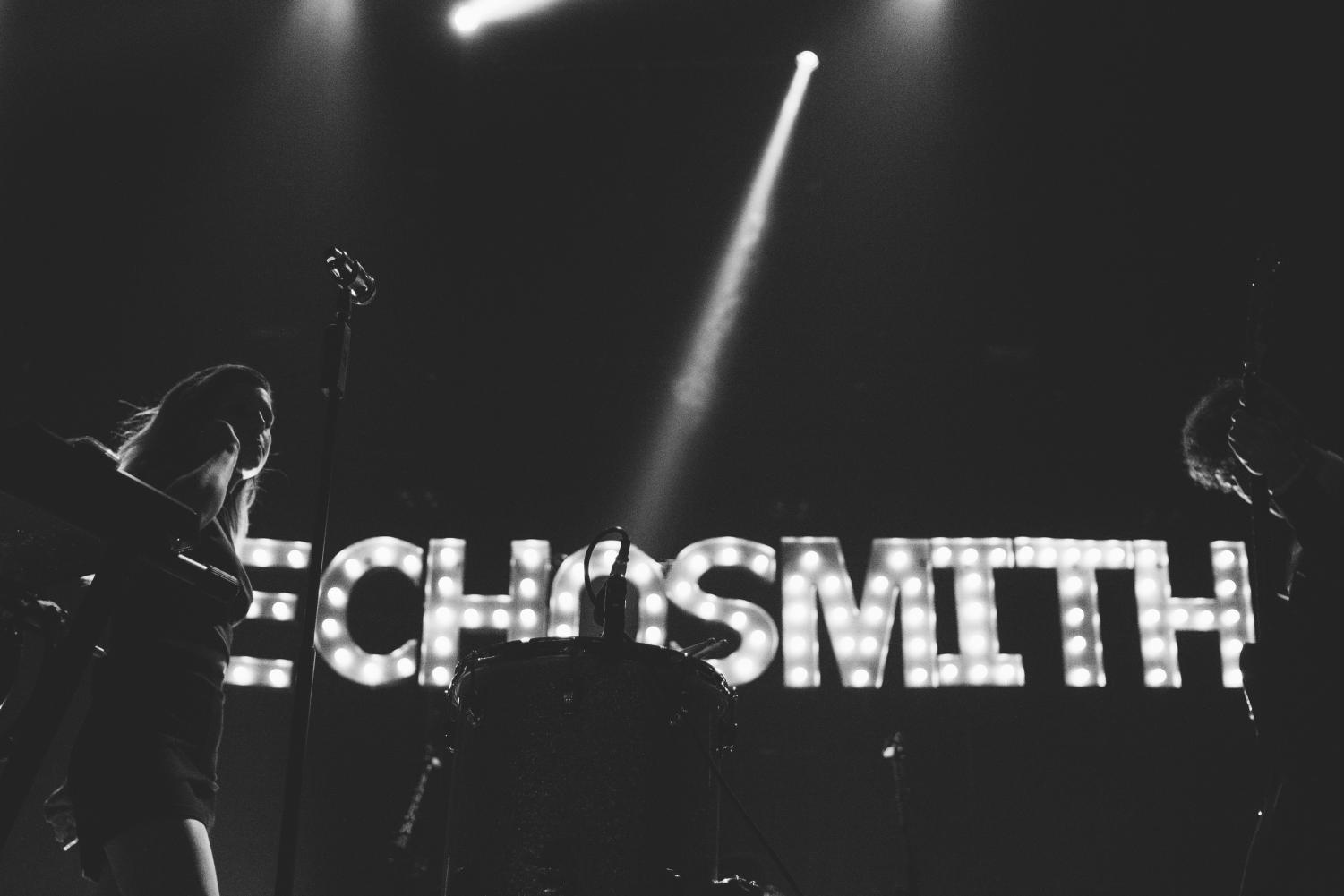 A performance by the band of siblings, Echosmith, shows their titled name flashing in the backdrop of the stage. (via Flickr under Creative Commons license).