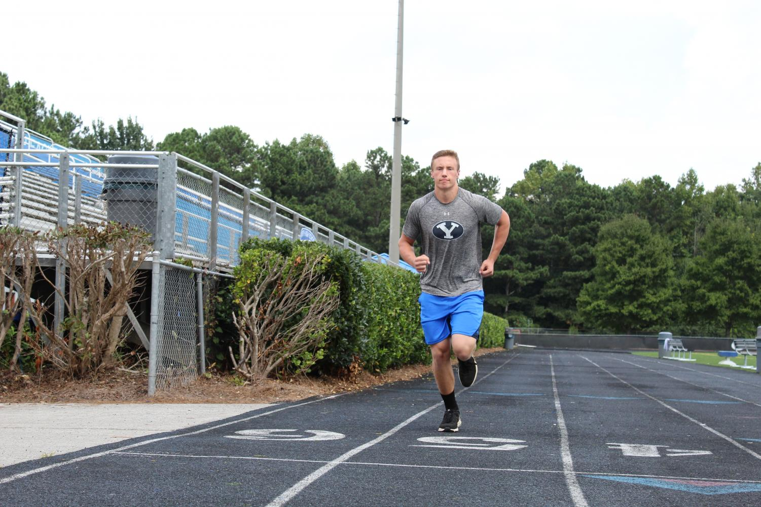 Taft Hilton, a varsity football player, runs the track at South Forsyth to warm up before practice.