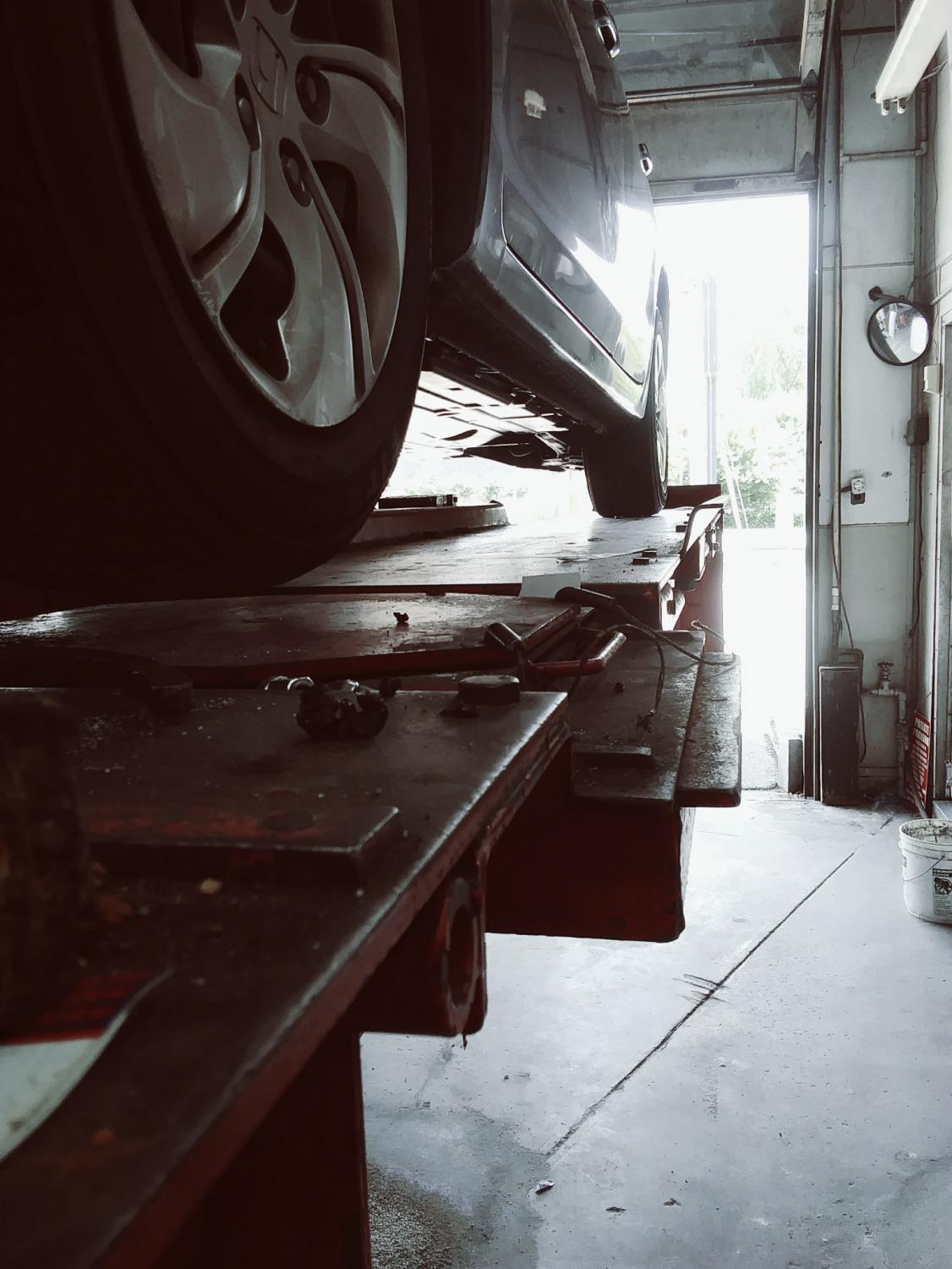 A Honda odyssey waits on the car lift for a tire alignment.