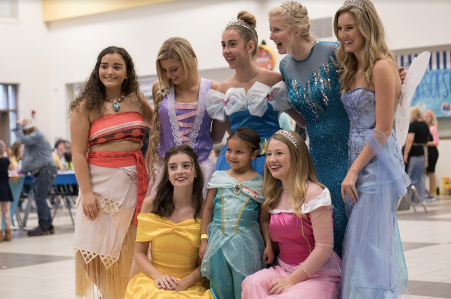 Picture-perfect princesses. In the cafeteria of Haw Creek Elementary, DECA members volunteer and dress up as Disney characters. The purpose of the breakfast event was to raise money for Burt's Big Adventure. DECA was able to raise a large sum of money for the charity organization.