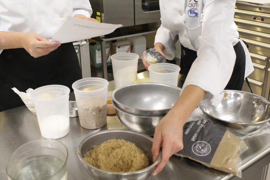 """Culinary students at work. Inside South Forsyth's culinary kitchen, culinary students prepare the sweet potato casserole. The students have been working on making the dishes since Friday. """"I think it's a great opportunity to help out the community and help out the people who we are serving,"""" stated Bythewood. """"And it's really fun."""