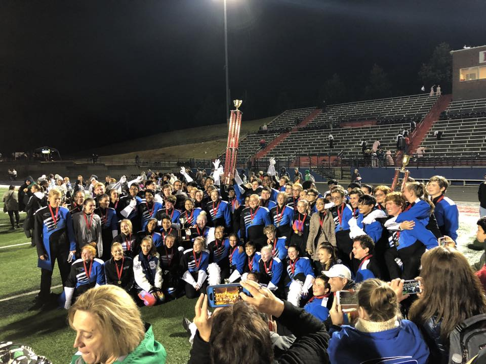 On the football field of Milton High School, the South Forsyth Marching Band gather once again for a group photo. That night, they celebrated as the new champions of the 2018 White Columns Invitational.