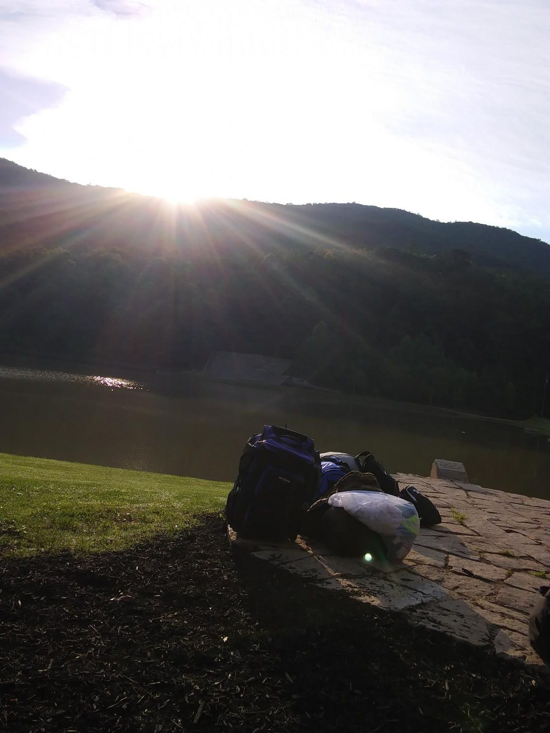 Sunrise in the valley. Outside of the Admin building, a camper's bag waits to be picked up and taken home after a week of adventure.