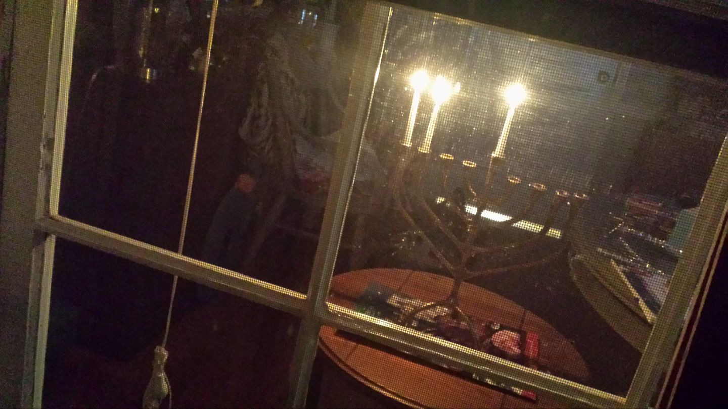 A glow in the window. The menorah is the traditional candle holder for Hanukkah; 9 candles are lit for each day of the holiday.