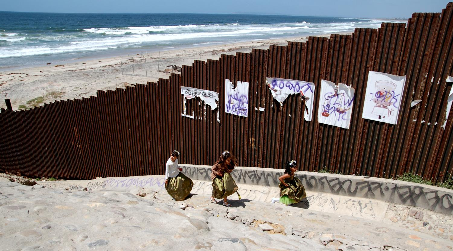 The Forgotten Ones. Playing alongside the wall, three little girls play along the US/Mexican border at Tijuana Beach, in Baja California, Mexico. Beknownstingly, it is unknown of where these girls came from or if they are parentless. Unfortunately, these girls are a small amount of the millions of the children that were left parentless during the procession of migrants.