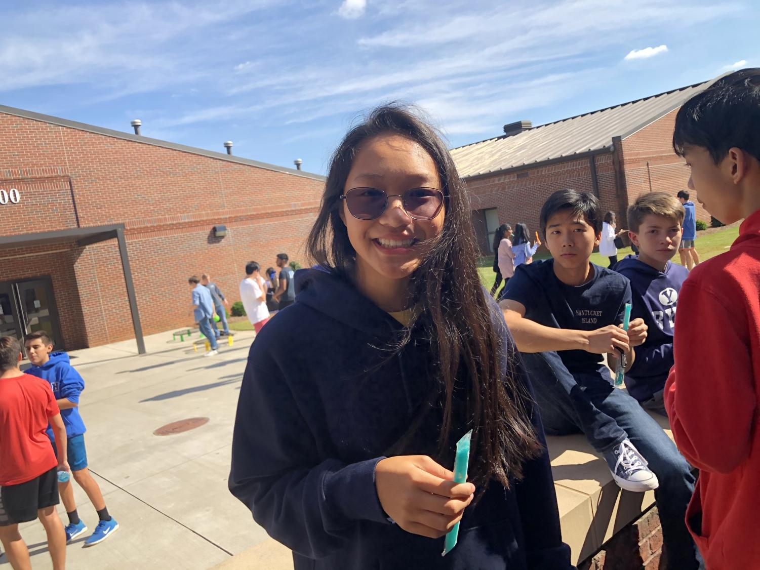 Tailgate with friends. Freshman Katelyn Kwak cools down with her popsicle underneath the warm sun. Faculty members passed out these sweet treats to students, eager to kickoff the  tailgate.