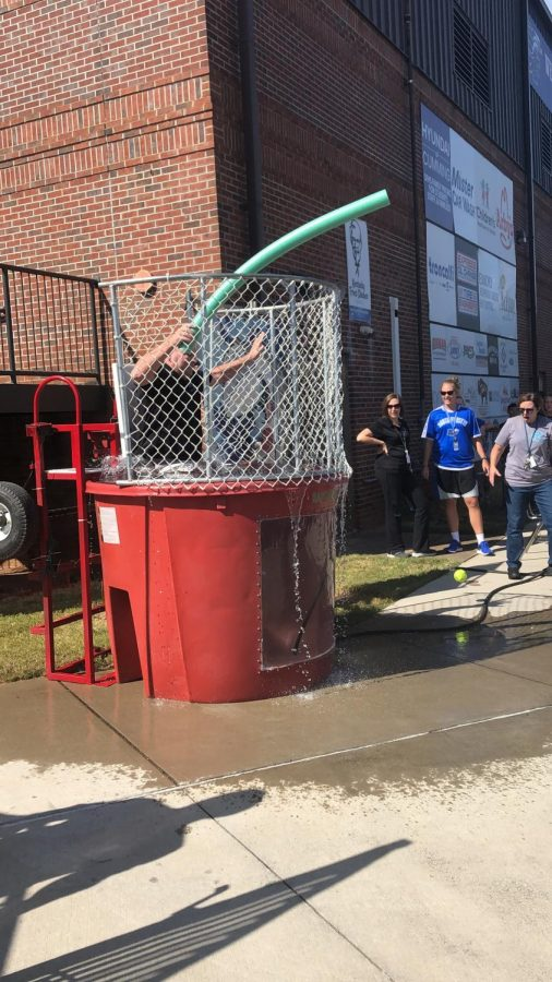 Time for a swim. Students could pay a dollar for three shots to dunk a teacher of their choice. By popular demand, Mr. Mac was persuaded to participate, with a line of students waiting to dunk him. The AP World teacher took it very sportingly, jokingly challenging students and even changing his profile picture to him in the tank.