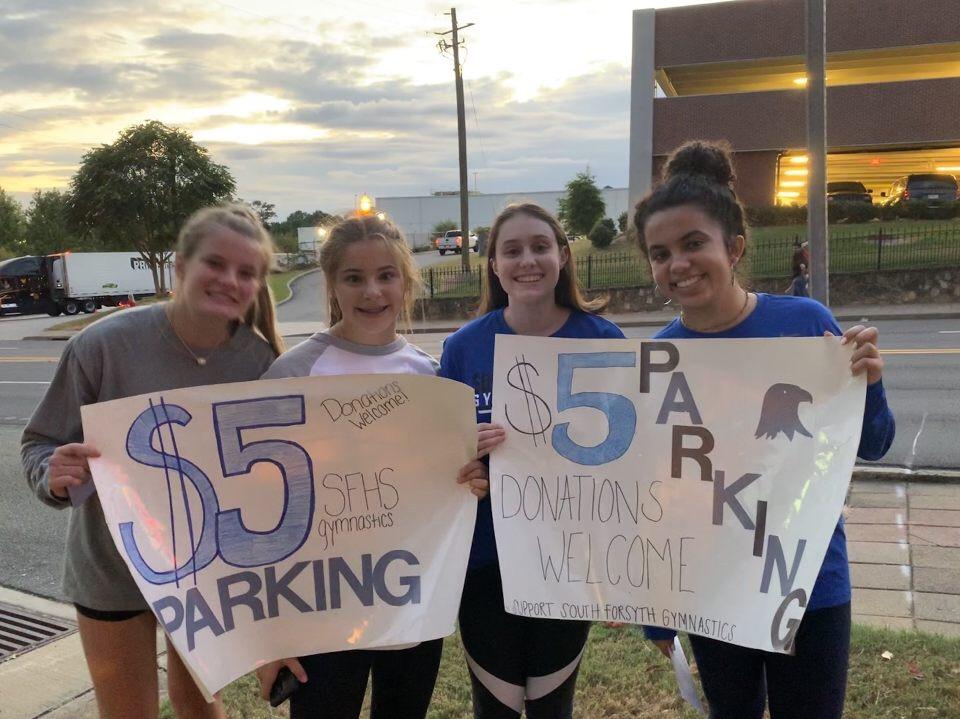 Junior Emma Knezevich, Freshman Carina Lefkovits, Senior Kelsey Watson, and Senior Sydney Goncalves wave signs together at the Cumming Fairgrounds. The money raised went to the gymnastics team.