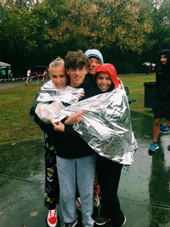 Bundle up. Mark Martin, Ansley Rogers, Emily Barnes, and Ashley Hunt cuddle up in the pouring rain. October 19th on a Saturday, runners from  South take on the speediest course and dominate it. The day being a mixture of rainy, and windy didn't stop them from running their hearts out on this meet.