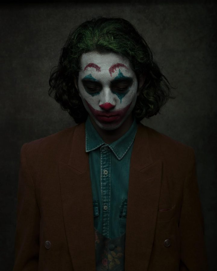 Man in Joker makeup. Posing in clown makeup for a shoot, the scene of the photo shows the darkness that surrounds the Joker character. Joker received great audience ratings on Rotten Tomatoes, with a percentage of 89%!