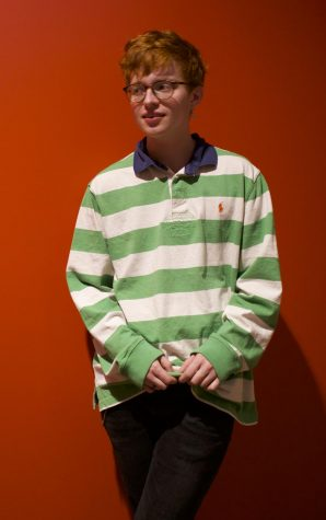 Artist photo. Robin Skinner poses in a green-stripped polo. Cavetown, Skinner