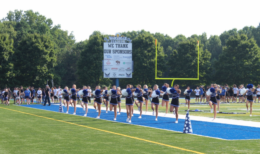 Cheering into the school year.  Students and teachers fill the stands with applause as they watch the cheerleaders perform their outstanding routine. The cheerleaders encouraged the students to join in on their cheers as they continued to fill the day with spirit.