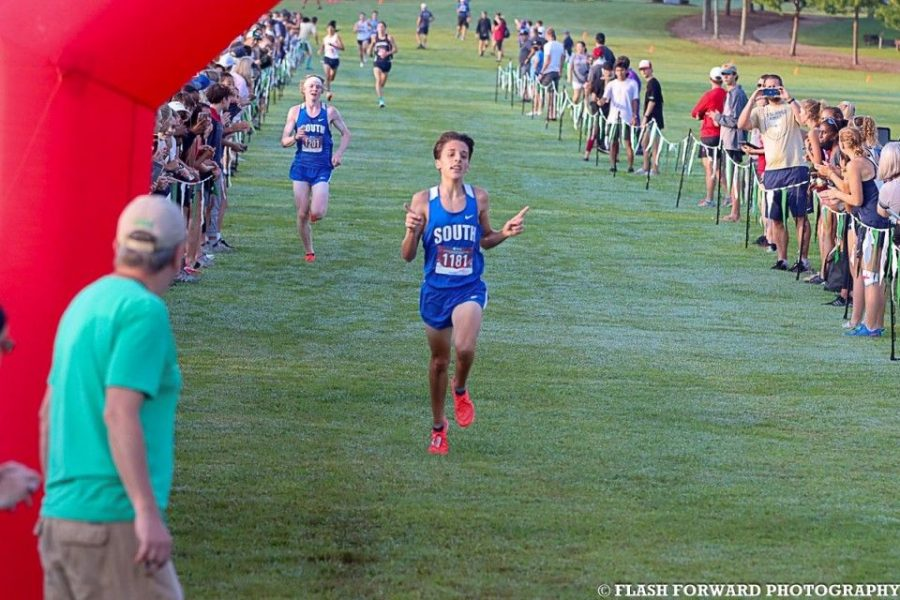 Boys varsity meet. Junior Ben Bergey leaps to the finish, leaving Nate only a few seconds behind. Bergey excitedly pointed his fingers up, and showed the sign for number 1 milliseconds before he crossed the line.
